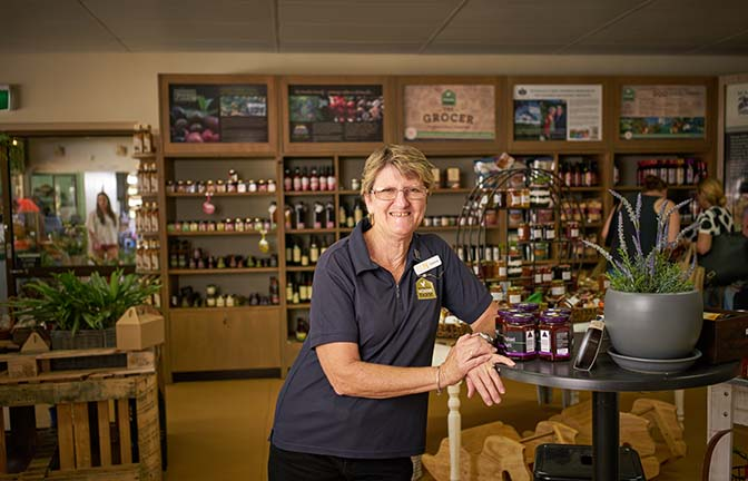 A smiling shop keeper stands next to shelves of produce