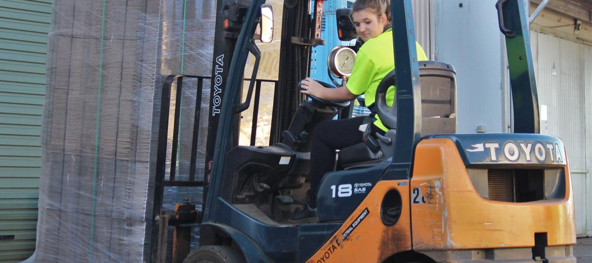 A worker drives a forklift to move boxes of produce