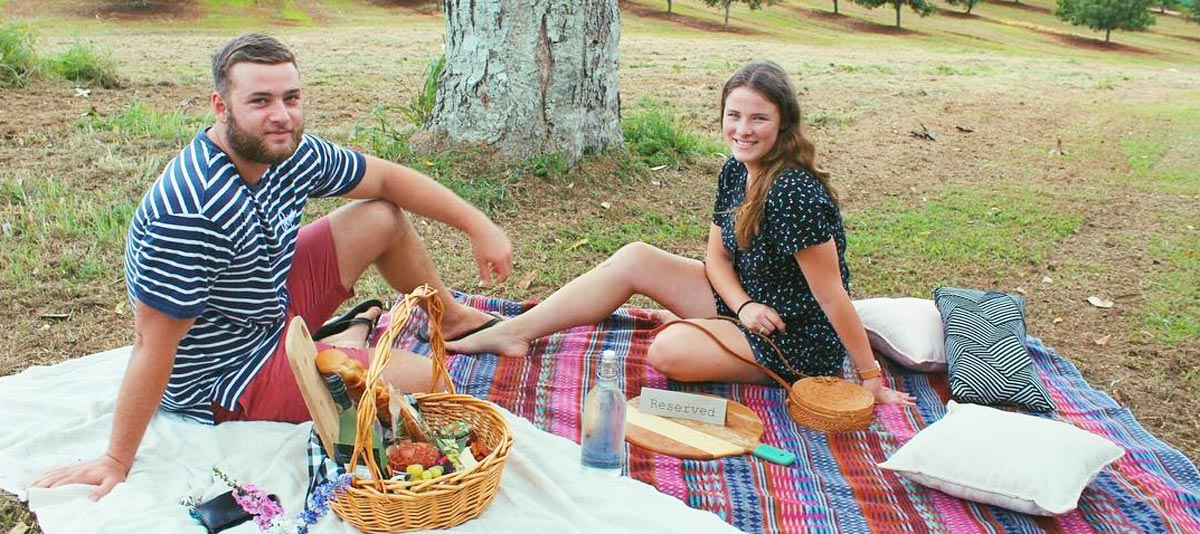A couple smiling at a picnic on a grassy hill