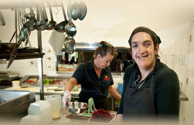 Smiling kitchen staff prepare food in a restaurant kitchen