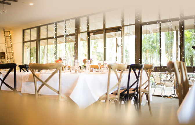 Tables set for a function in a bright room with high windows