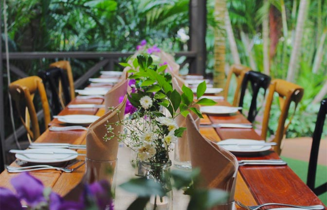 A polished wood table set with colourful flowers in an alfresco setting