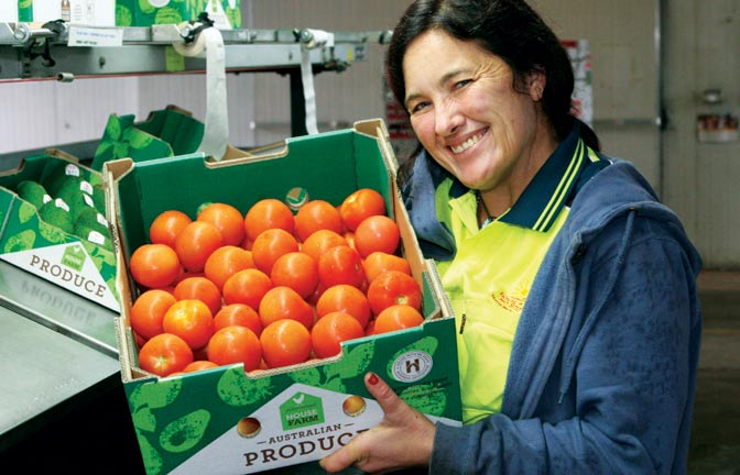 A smiling worker holds a box of tomatoes