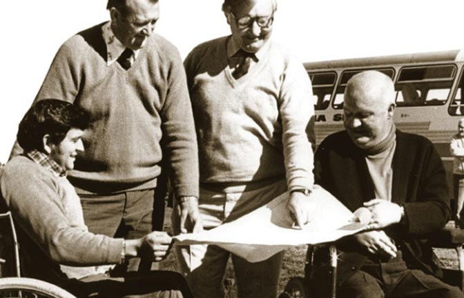 Lionel Watts reviews plans with partners as the farm is built