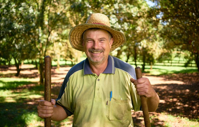 A smiling staff member with a disability stands with tools in an orchard