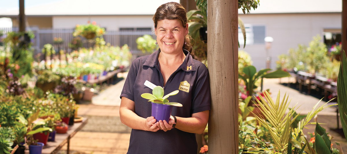 A smiling nursery worker holds a potted plant in a nursery