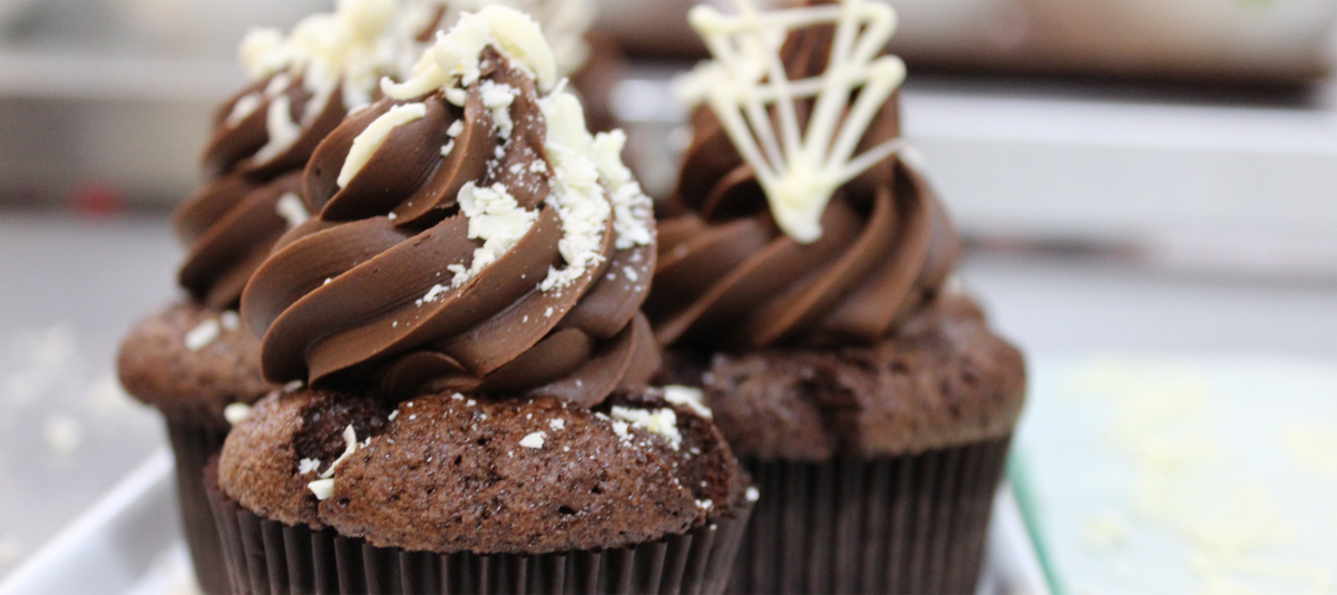 Rich chocolate cupcakes with decorative white garnishes