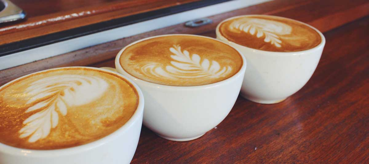 A row of cappuccino coffees in white cups