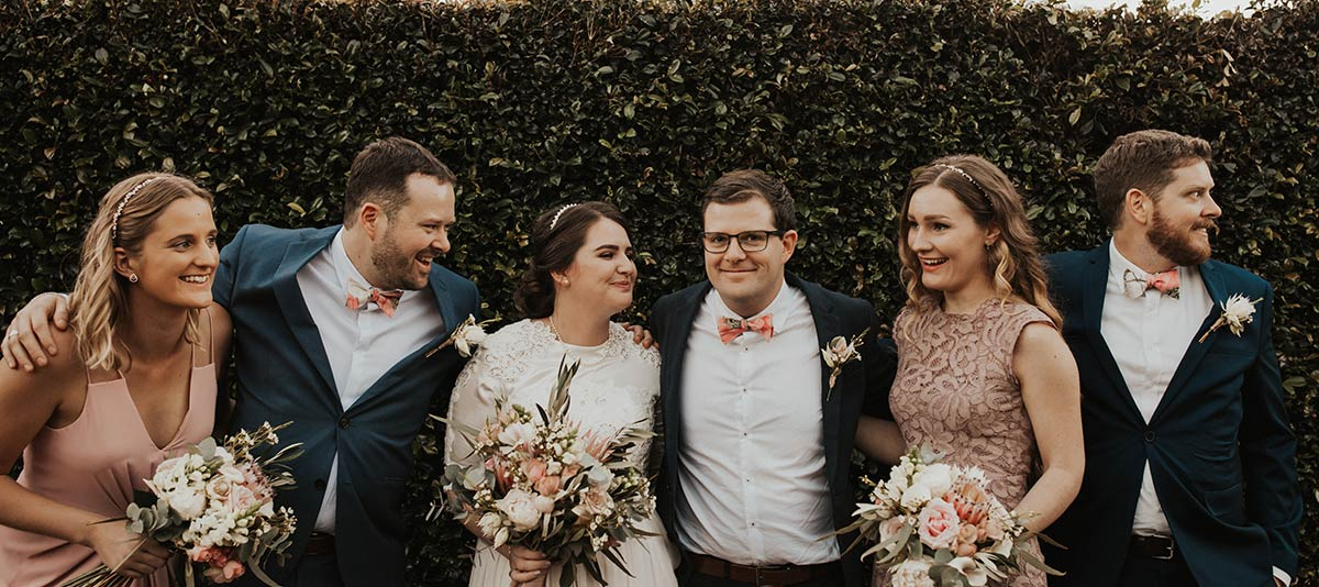 A wedding party poses candidly in a garden