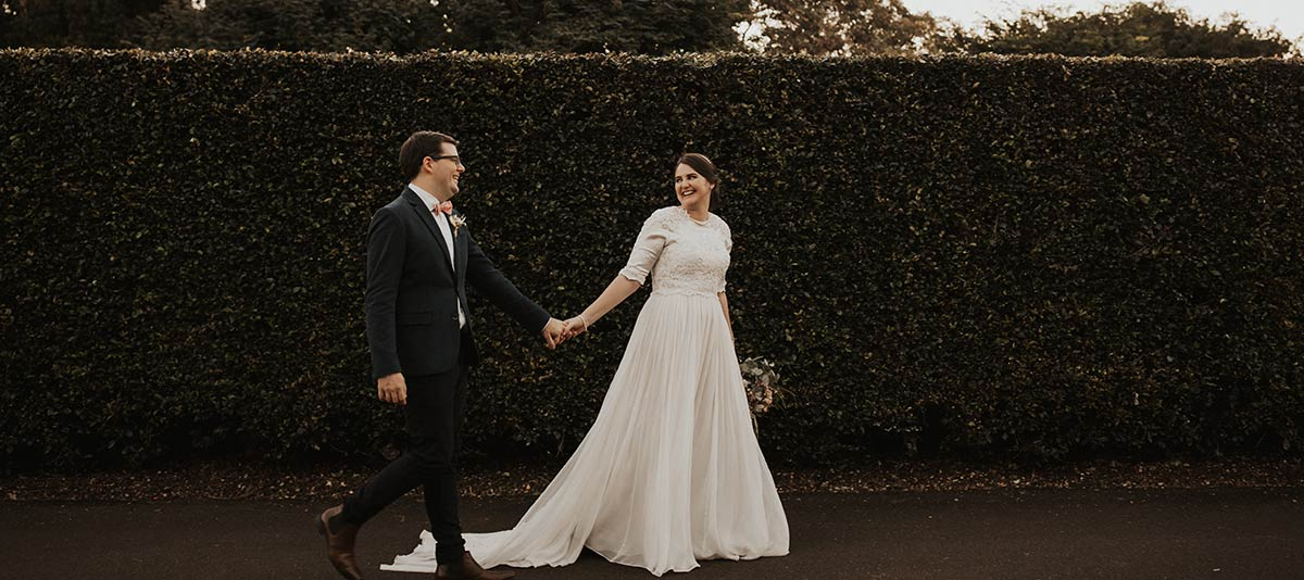 A bride and groom walk beside a picturesque hedge