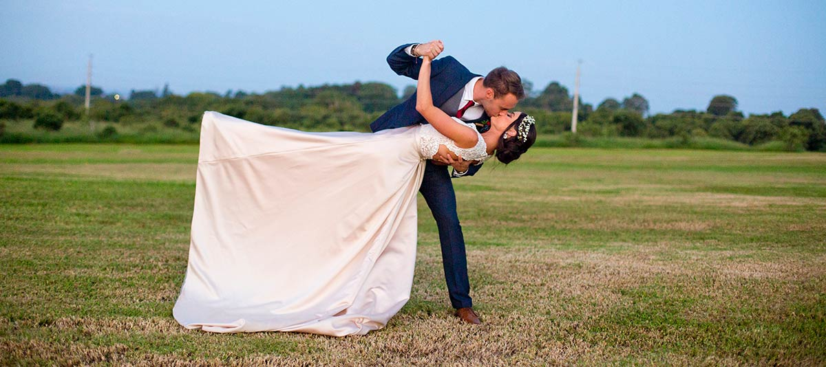 A bride and groom pose in a green field