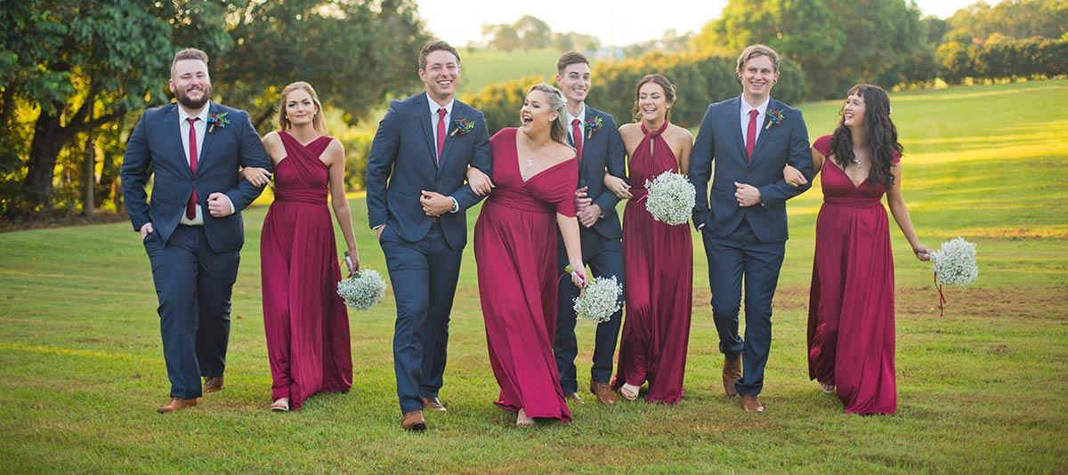 A smiling wedding party walks across a green field