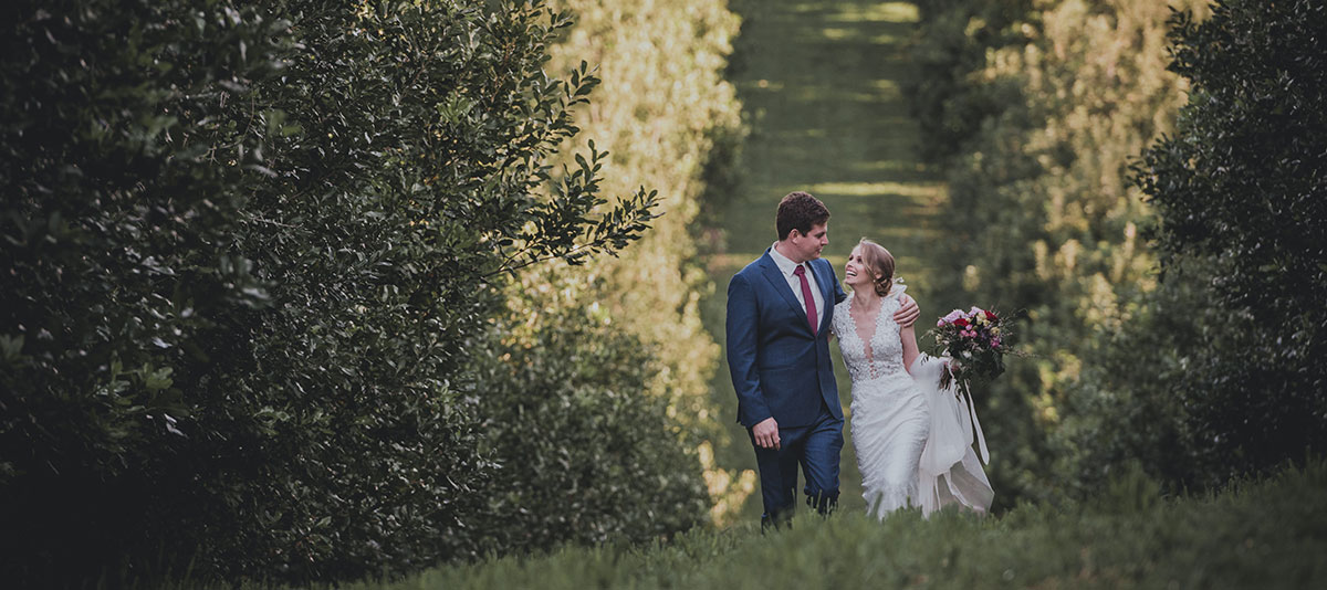 A happy bride and groom walk through an orchard
