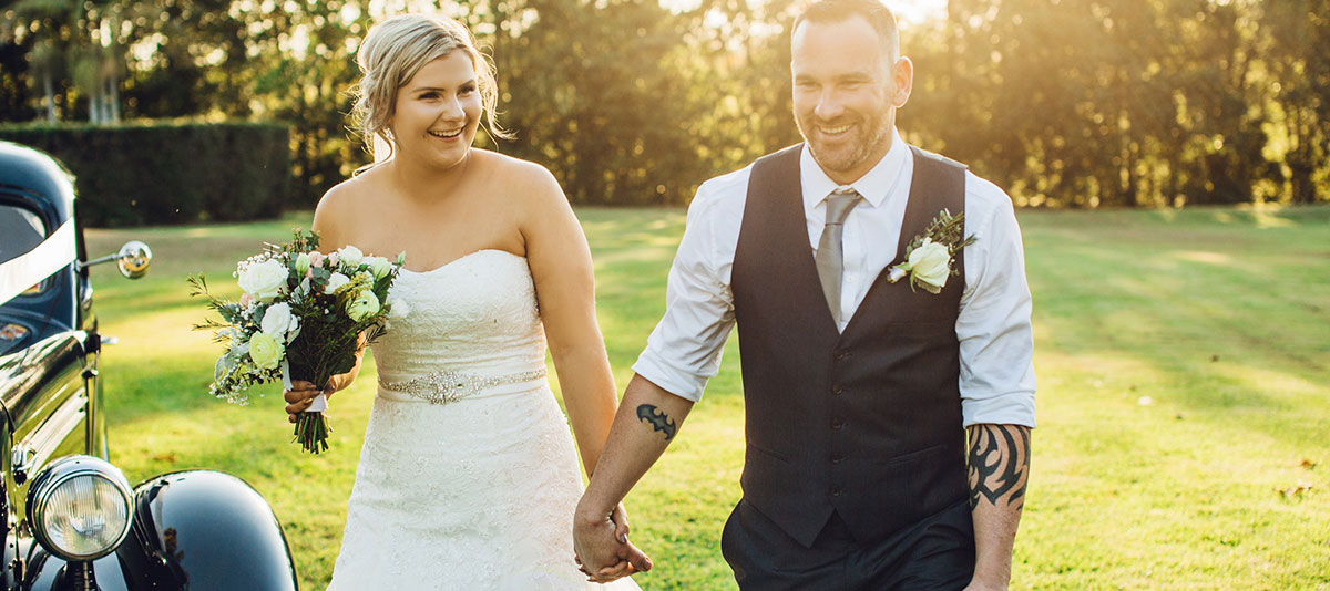 A smiling bride and groom walk hand in hand to a vintage car
