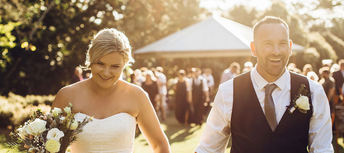 A smiling bride and groom walk hand in hand