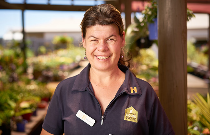 A Summerland Farm employee with a big smile on her face. She is wearing her uniform.