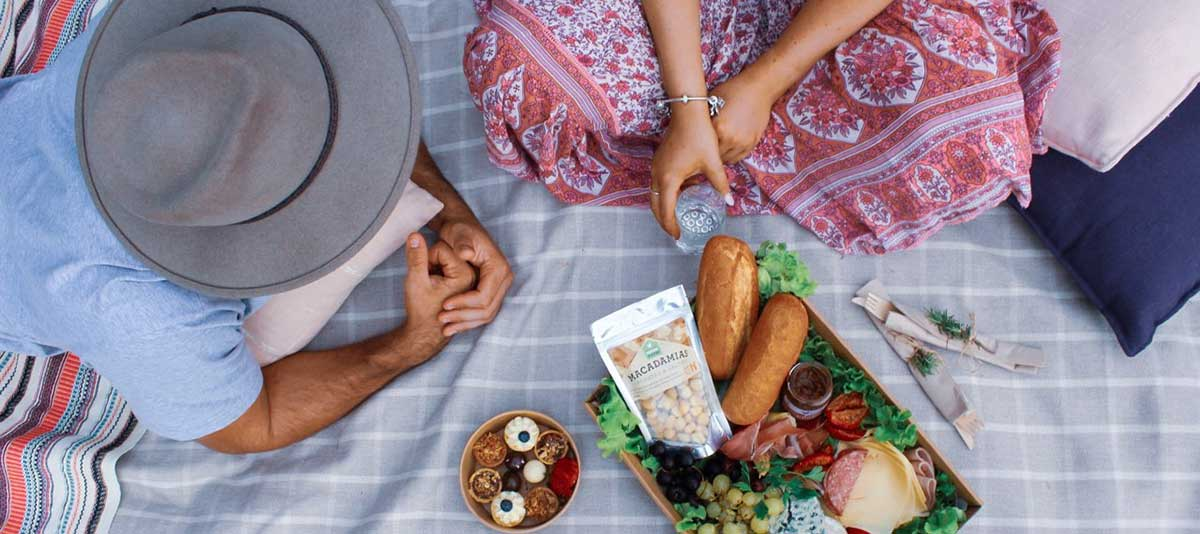 A couple sharing a picnic box of gourmet food