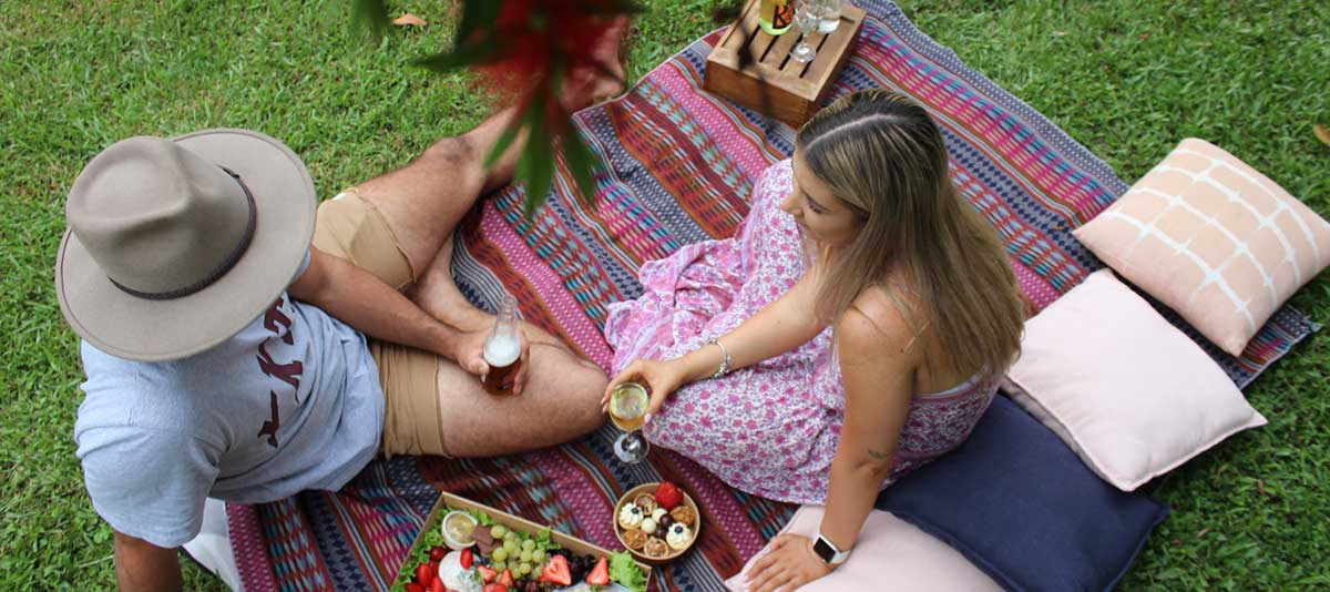 A couple enjoys a gourmet picnic under a tree on a grassy lawn