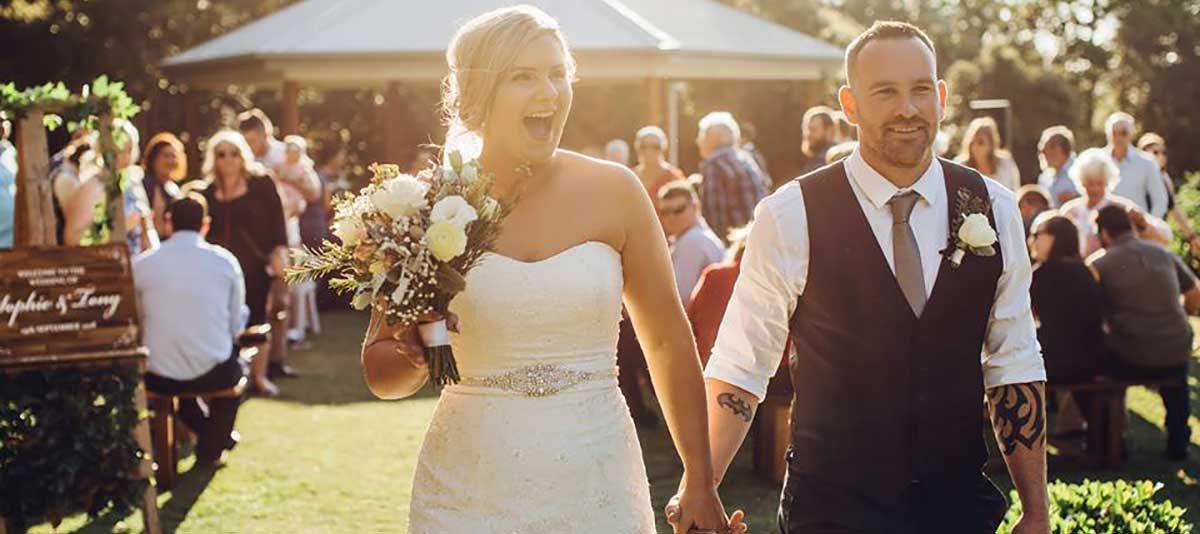 A bride laughing and walking with her groom from the Rotunda at Summerland Farm