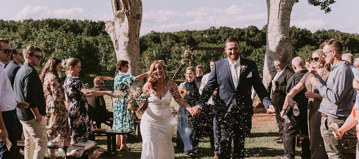 A newly married couple walk through confetti at Summerland Farm