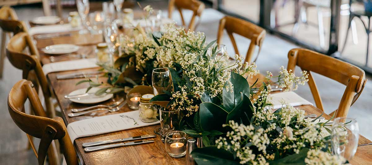 Wedding flower arrangements and candles in the Function Room at Summerland Farm