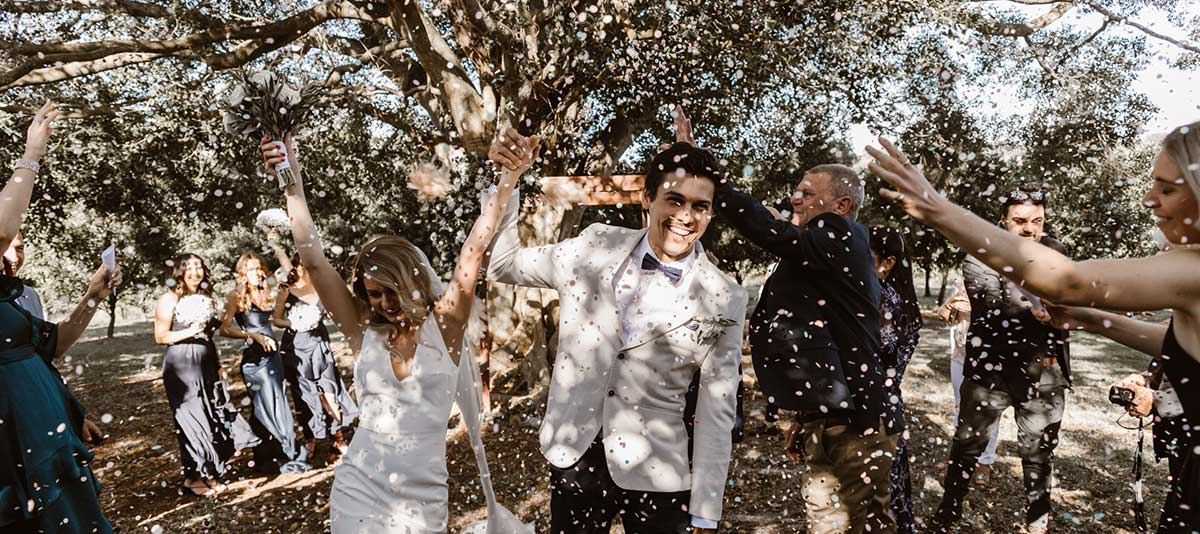 Newly weds walk hold hands walking through a halo of confetti at Summerland Farm